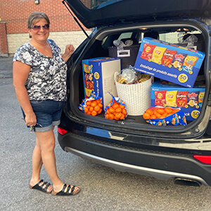 Woman standing beside open van with oranges and other food items stacked inside