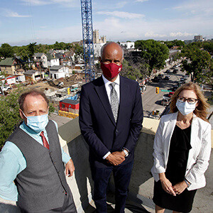 Three people on roof facing camera with construction in background