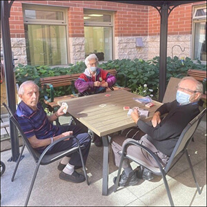 Three people sitting outside at a table playing cards. They are in a garden setting.